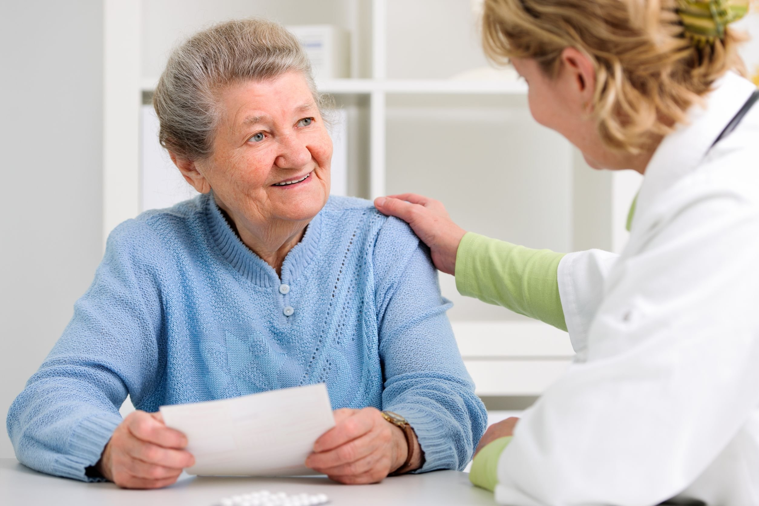 Older woman comforted by medical staff
