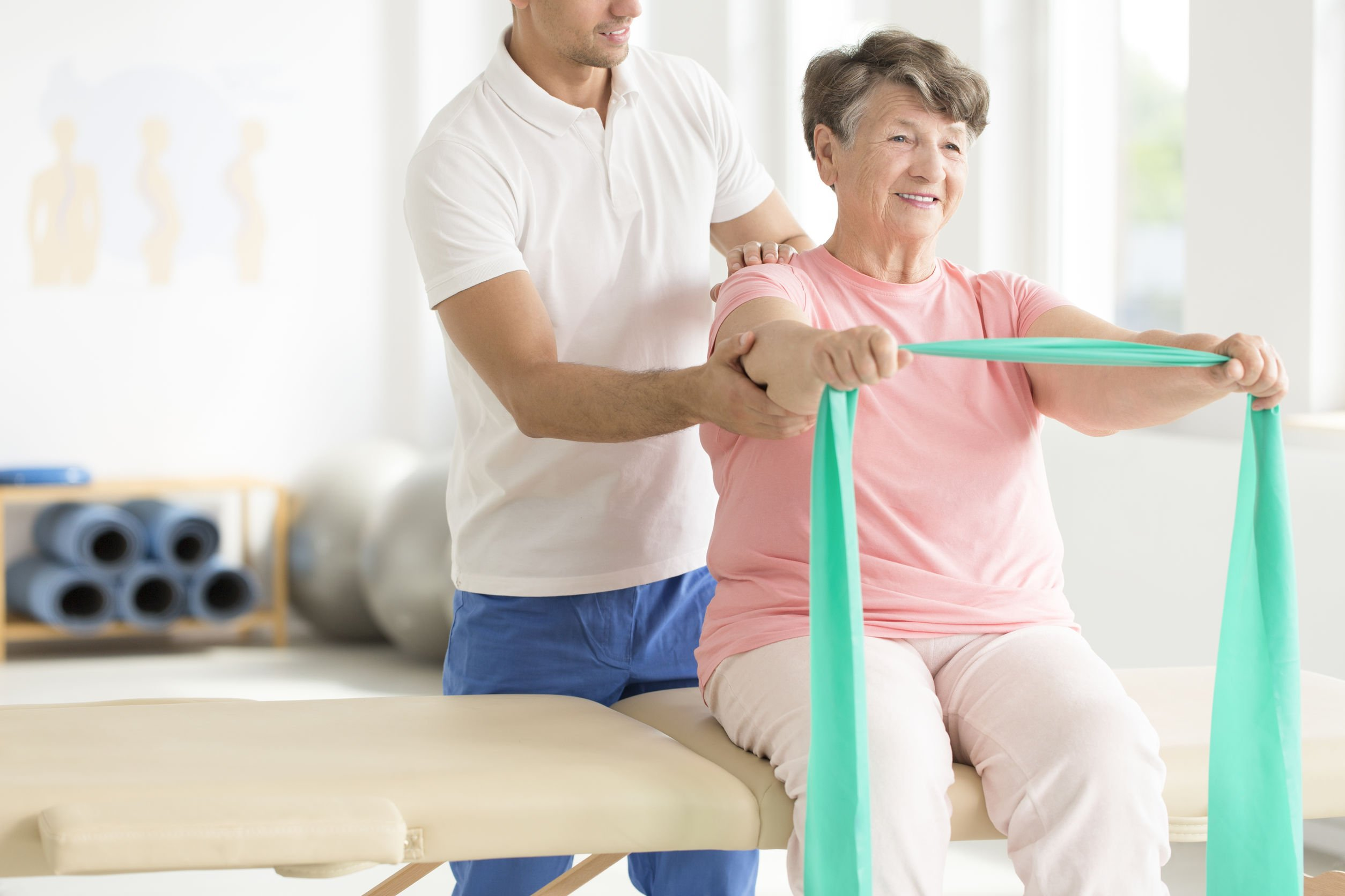 older woman working out with band and physical therapist