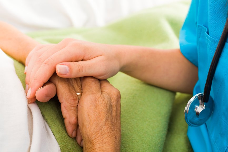 nurse holding hands with elderly patient