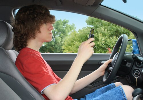 Teen Driving with a cellphone in his hands