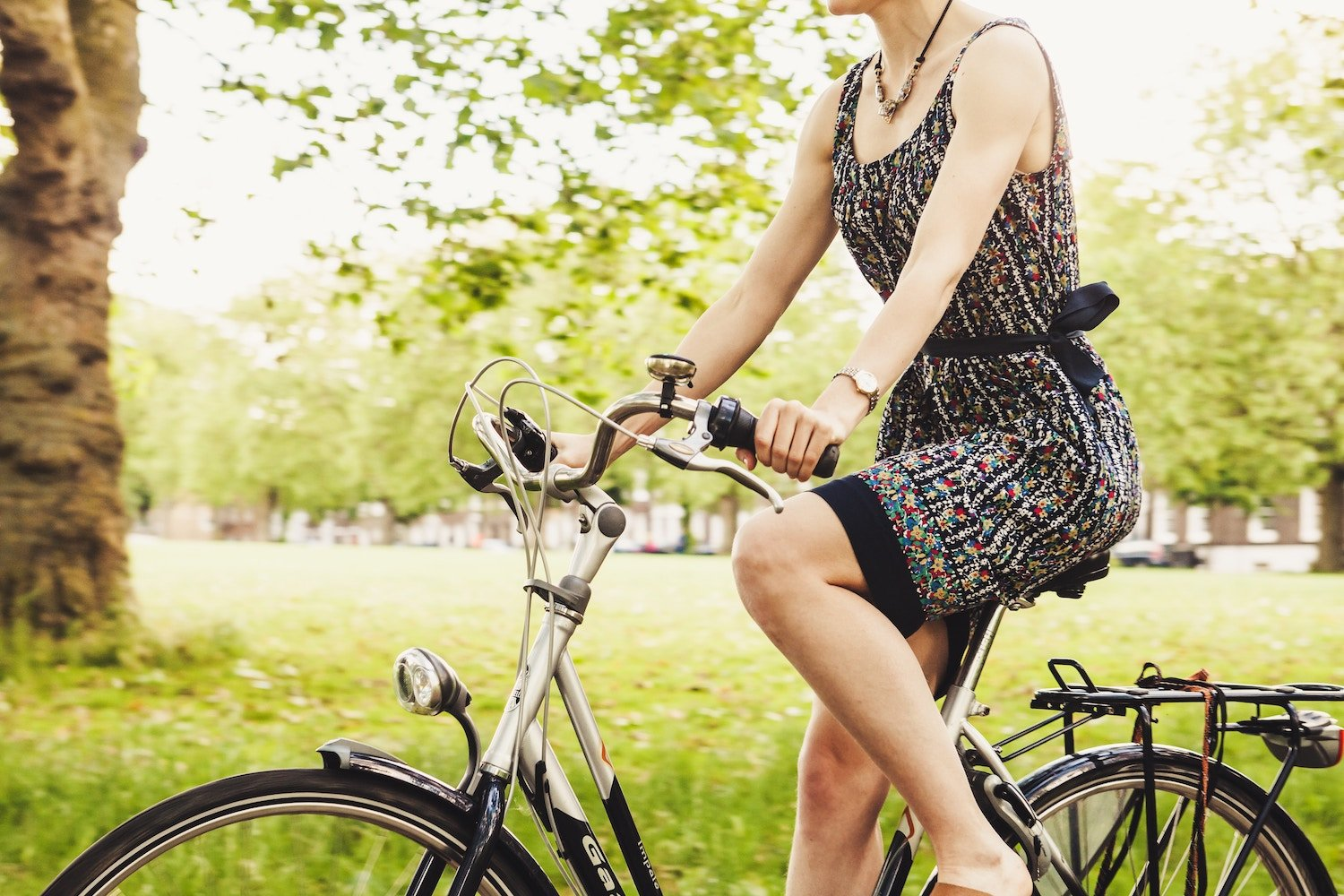 girl in dress riding a bicycle in a park
