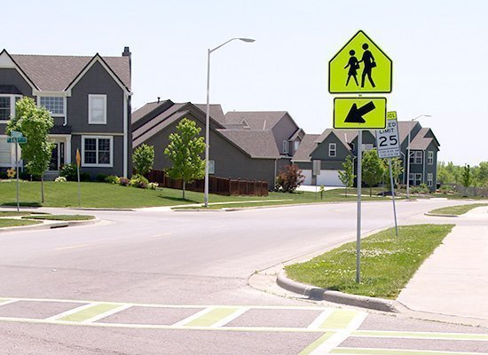 Photograph of a school zone crossing sign and a crosswalk in a residential neighborhood.