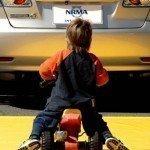 child playing behind car