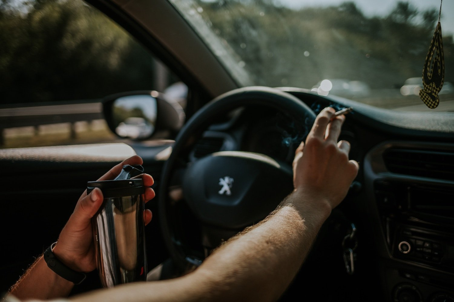 man driving distracted by drinking and smoking driversed.com