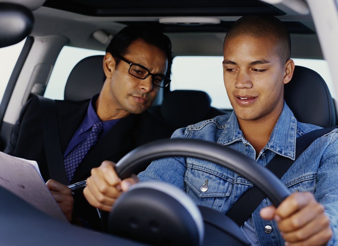 Driving instructor observing learner driver