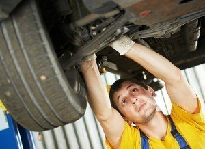 mechanic performing maintenance on lifted car