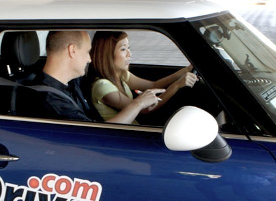 A uniformed DriversEd.com instructor helps a student learn to drive the safe, SMART way.