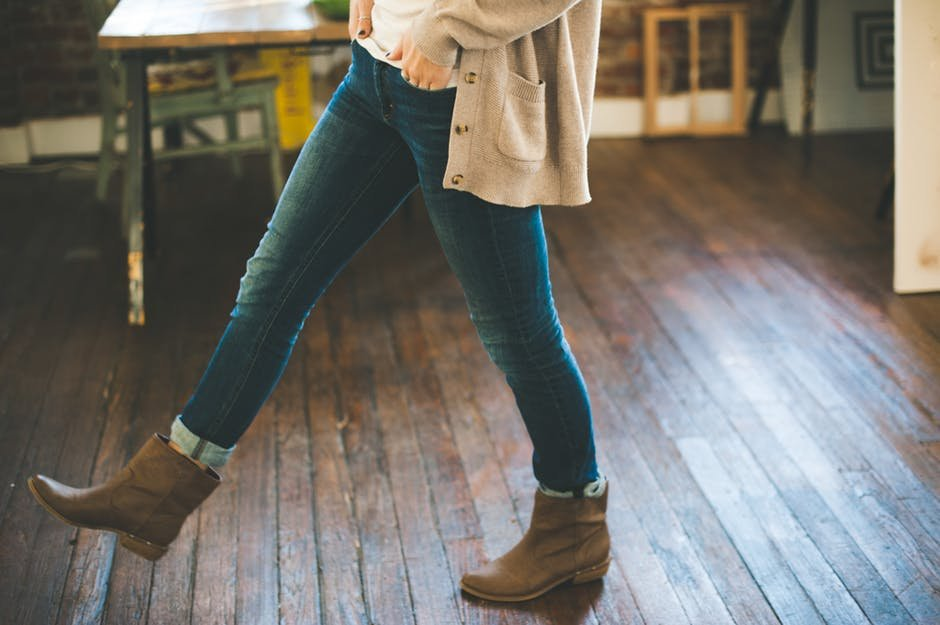 Woman wearing jeans trying to figure out how to make pants bigger
