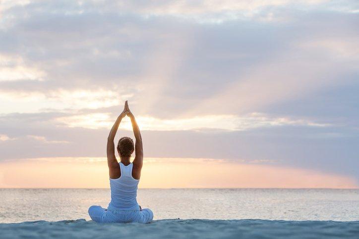Woman doing yoga facing the sunset. JOI
