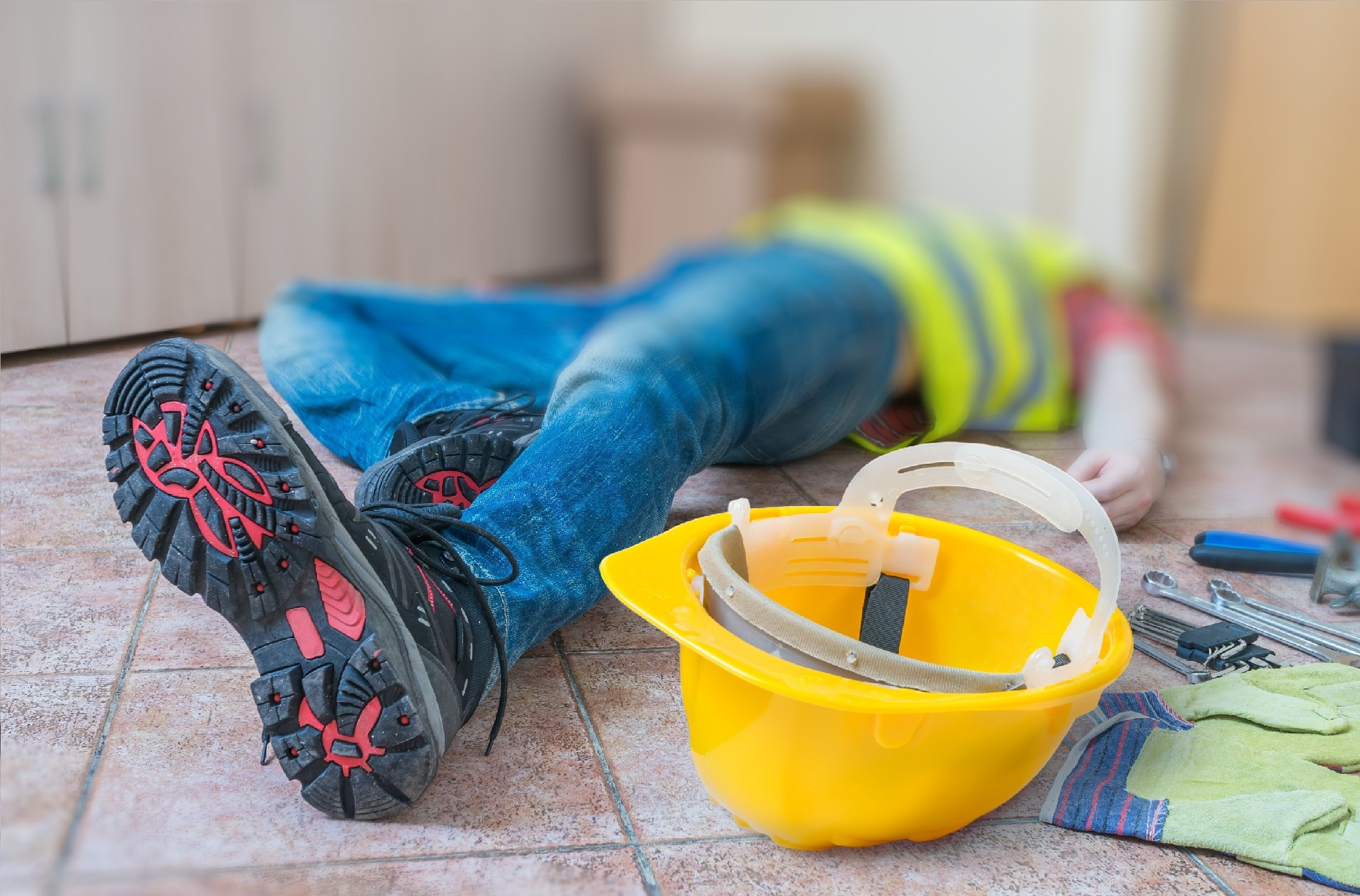 Construction man with secondary health insurance laying on the floor after an accident