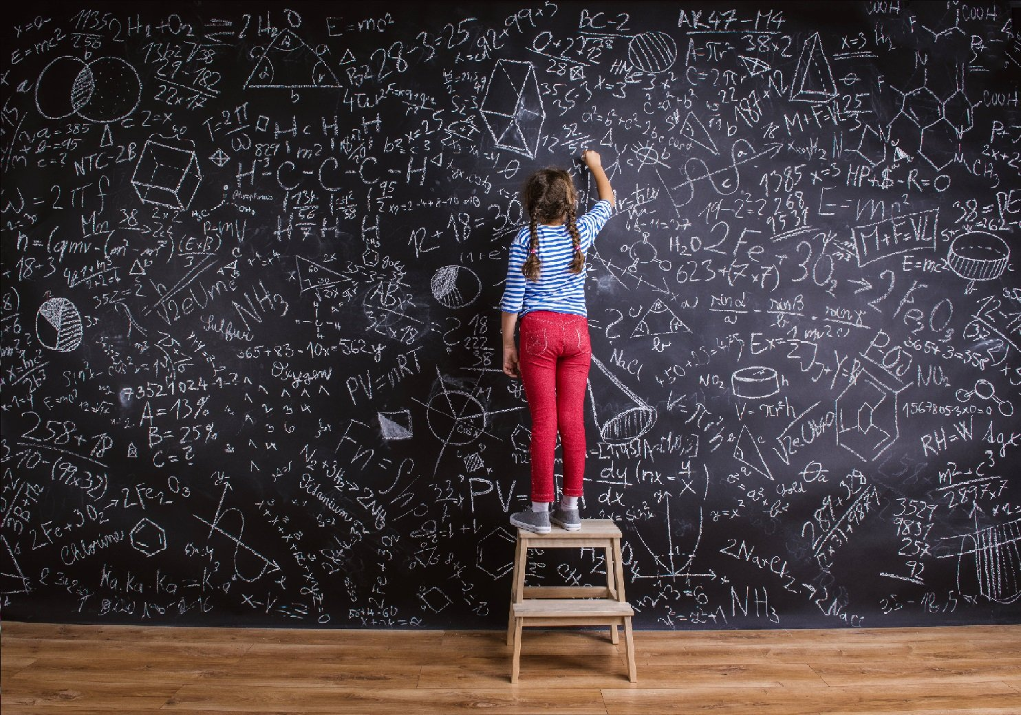 Young girl with supplemental accident insurance and pigtails wearing red pants standing on stool writing on chalkboard