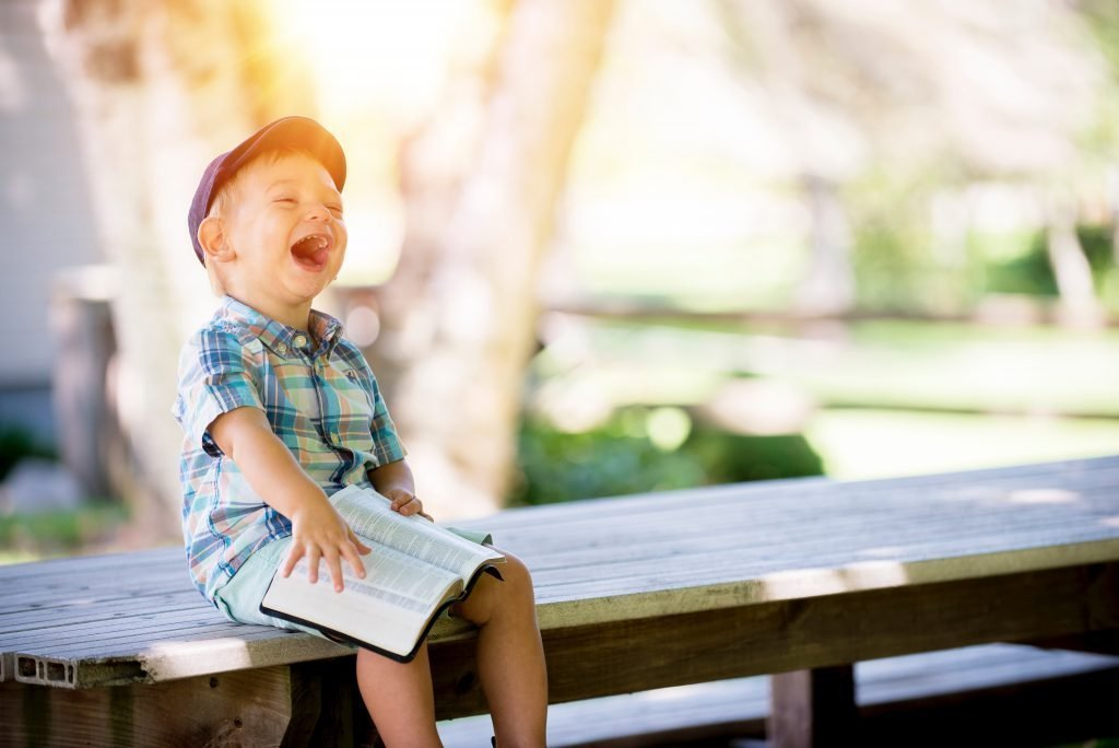 boy-holding-bible-while-laughing