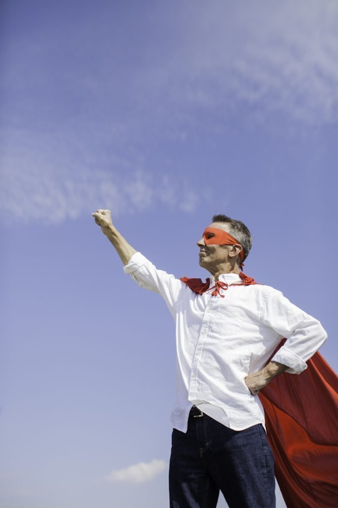 man posing as superhero with cape and maskspace for textlightstockvertical