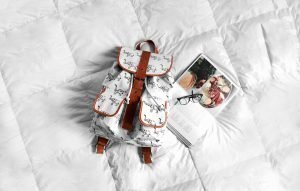 Backpack and recipe book on white bed