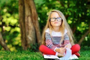Blond girl with glasses reading